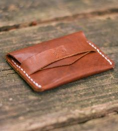 Made minimalist to carry just the essentials, this small leather wallet neatly fits your most important cards and some bills. The card holder has a single pocket and closes with a single flap, which tucks underneath a small strap. Each one's cut, grooved and stitched by hand, and the fully enclosed design ensures everything stays secured inside.
