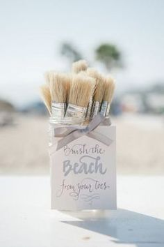 Paintbrushes with a sign indicating guests should take one to clean the sand off their toes.