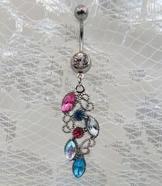 Belly button piercing ring with lovely teardrop dangle containing clear, pink and blue larger Czech marquis shaped crystals and smaller round crystals on a silver ornate teardrop dangle. The ornate si