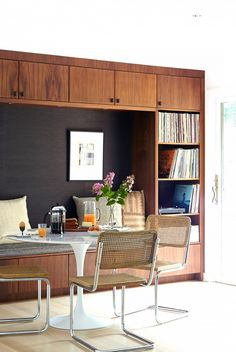 Masculine dining space with a built-in wood feature wall, bench seating, silver and wood chairs, and hardwood floors.