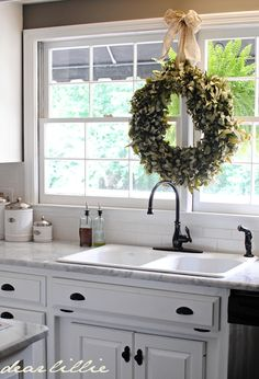 I need a wreath over my kitchen sink and I love the fern hanging outside the window. Love the touches of green. ...from Dear Lillie's blog