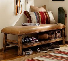 Rich rustic leather bench with bronze nailheads and wood shelf for storage.