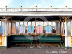 Promenade shelter with beach huts behind in Hove, UK.