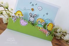 """Lawn Fawn Chirpy Chirp Chirp Stamp Set...For the inside of the card, I adhered the second """"sky"""" stitched rectangle die to the inside top of the card. The Stitched Hillside Pop Up and Grassy Hillside Pop Up Add On were die cut from Lawn Fawn Cilantro Cardstock and assembled and adhered to the inside of the card as shown. The stamped, colored, and die cut Chirpy Chirp Chirp Stamp Set and the bunny from the Hoppy Easter Stamp and Die Set were adhreed to complete the inside scene."""