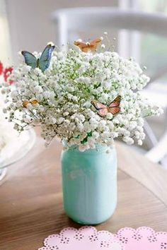 Pretty idea for a wedding or shower. Painted mason jars with Babies breath and butterflies.