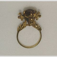 Ring  14th century  Gold ring, the pyramidal bezel nielloed with a flower on each side and set with a cabochon ruby, the circular hoop decorated with niello scrollwork, the shoulders terminating in dragon's heads  16.71 mm internal ring diameter; 8.1 g weight