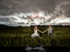Bridal couple in a cornfield with magnificent cloudy sky backdrop
