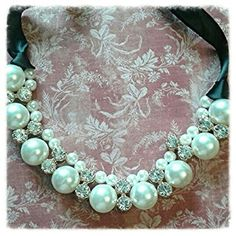 Faux Pearl and Rhinestone choker necklace This is a great little necklace.  It is my go to pieces when I'm in need of some bling. It's classy and timeless I put it with dresses in the hot months and sweaters in the winter time.    It does not have a clasp it is a ribbon tie closure. Jewelry Necklaces