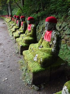 Jizo protector statues, Kanmangafuchi Abyss..Japan..... A long series of jizo protector statues on the side of a hill, some adorned with hats and bibs, some crumbling with age, with a river, small waterfalls and rapids below. Legend says that the statues change places from time to time, and a visitor will never see them in the same order twice... by Caenwyn, via Flickr
