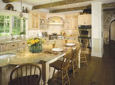 The contemporary kitchen that Susan Rochelle designed is right at home in the farmhouse-style home. Open to the family room and dining area, the kitchen has maple cabinetry with a white glaze, a large island and granite countertops in shades of rust, gray and silver. An antique-style plank door off the family room leads to the basement.