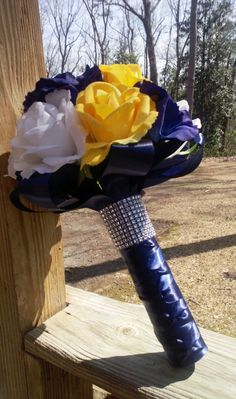 This listing is made to order and Includes 1 Bride's 10in Round Bouquet with Real touch Yellow Roses, White Roses, and Silk Navy Blue Roses wrapped in Your choice of satin ribbon with Rhinestone wrap