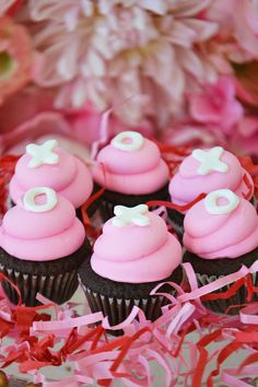 Chocolate XO Mini Cupcakes with pink icing on a bed of red and pink sizzle. By Bake Sale Toronto.