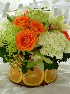 Citrus Centerpiece. Most of this minus maybe the Roses. Add a bit darker green. Citrus leaves or Pittosporum...?