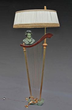 Elegant neoclassical #lamp ArtDeco. Structure in #bronze and #gilt #brass forming a large ornate harp. Atop a varnished wooden stick with a bust of #Beethoven in green patinated metal. Signed G. #LEROUX. Circa #1940-1950. For sale on Proantic by Galerie Tramway.