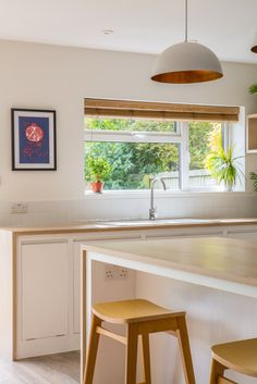 """Minimalist White Kitchen in 1930s Semi-Detached House in Somerset, U.K. by Sustainable Kitchens - """"The owners' two teenage children often eat breakfast at the large island, so there are plenty of electric sockets built in for their tablets and mobile phones."""""""
