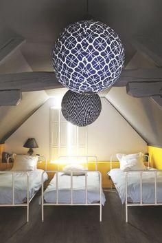Quant à la chambre des enfants, elle a été pensée comme un dortoir, avec trois lits, AM.PM. Suspensions en forme de globes, Bonton.