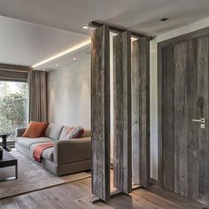 L'utilisation d'une cloison partielle ajourée en bois brut vielli délimite l'espace