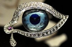 Brooch/timepiece designed by Salvador Dali --The Eye of Time, 1949.  Blue enamel, diamonds, platinum and cabochon ruby. The eye opens to reveal a blue-faced watch.