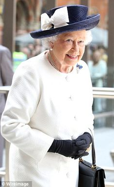 On the way: The Queen left London in a neat cream coat and a navy hat with a huge cream bo...