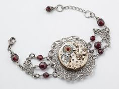 Steampunk Bracelet Neo Victorian vintage watch movement gears silver filigree garnet red crystal Steampunk jewelry by Steampunk Nation 1887. $99.00, via Etsy.