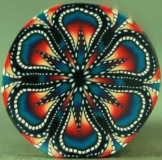 Love the colors in this cane. Polymer Clay Circle Kaleidoscope Cane 'De Colores' by ikandiclay.
