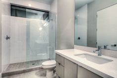 Frameless glass shower + grey painted cabinets + white countertops | contemporary bathroom