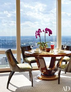 A family room dining area featuring Art Deco side chairs , an ebony table and views of Manhattan   archdigest.com