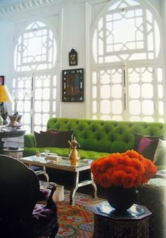 Love everything about this living room, windows, green couch, orange flowers, patterned carpet..