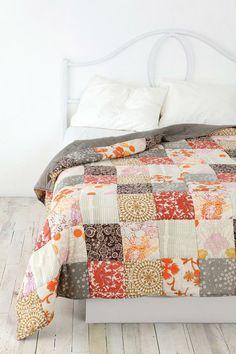 Witte slaapkamer met vrolijke quilt op bed.