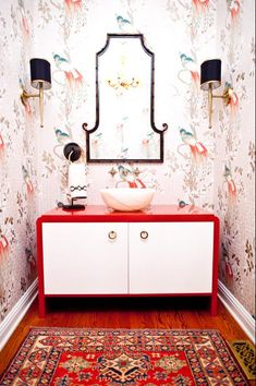 red and blue chinoiserie wallpaper, red and white console, black chinoiserie mirror, black sconces