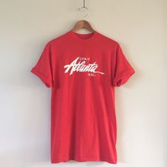 "Atlanta Vintage Tee Lipstick red tee with ""Look at Atlanta Now"" white text. This was a promotional slogan for the city to bring in tourism. Nice soft worn in feel with graphics starting to crack. This would be great cut as a muscle tank!  BRAND: Touch of Gold MATERIAL: 50/50 YEAR/ERA: late 80s / early 90s LABEL SIZE: XL  MEASUREMENTS: Bust 19 inches Length 28 inches  ☠ No trades please!  Check out my closet for more vintage tees! Vintage Tops Tees - Short Sleeve"