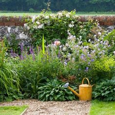 96_0000121db_d893_orh550w550_Flower-border-and-brick-and-flint-wall-in-English-country-garden