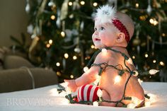 Baby wrapped in Christmas lights