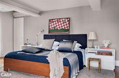 Linhão azul-marinho compõe a cabeceira acolchoada. O tecido é da Orlean, que também forneceu o papel de parede cinza. Mesas laterais da Quarto Composto, mantas da Trousseau e do Empório Beraldin.