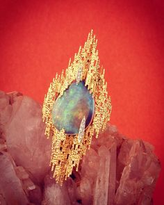 An Australian opal set as a brooch in yellow gold textured wire and diamonds. By Andrew Grima 1970s