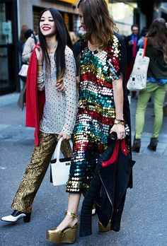 Patty Lu in embellished gold pants and Megan Bowman Gray in a sequin dress and gold platforms.