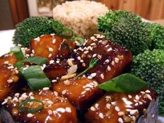 Vegan Sesame Tofu1 package extra-firm tofu, drained and pressed 1/2 cup arrowroot, divided 1/4 cup cold water 2 Tbs. peanut oil, divided 4 cloves garlic, minced 1 Tbs. fresh ginger, minced 4 Tbs. mirin or rice wine 2 Tbs. gluten-free tamari 2 Tbs. Hoisin sauce 2 Tbs. agave nectar 2 Tbs. spicy chili sauce Zest of one lemon 2-3 Tbs. sesame seeds 2 Tbs. scallions, finely sliced