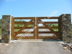 wooden driveway gate... but paint it white & buy the electric/solar kit w/ keypad entry