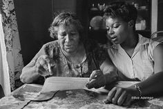 """Ann Beattie on Bob Adelman's photography of the Civil Rights Movement. Pictured: """"CORE Volunteer Helping an Older Woman Learn to Fill Out a Voter Registration Form, East Feliciana Parish, LA,"""" 1963."""