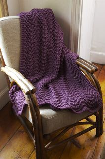 This cushy ripple afghan is perfect to snuggle under while watching TV or reading a great book. (Lion Brand Yarn)