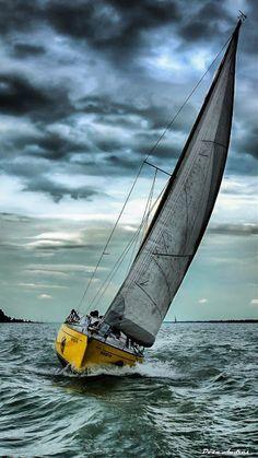 Zeil boot op het water bij donker weer.