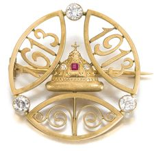 An Imperial Presentation Fabergé jewelled gold Tercentenary brooch, Moscow, 1913. Circular, centred with a rose-cut diamond- and square-cut ruby-set Cap of Monomakh, within three large circular-cut diamonds and ellipses pierced with scrolls and dates 1613-1913.