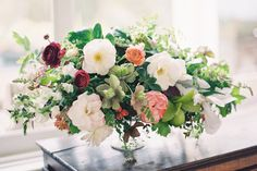 love these centerpieces! low so guests can see over them but still full and abundant!