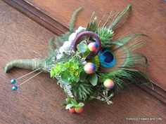 Boutonniere with blue laser hypericum, fern curls, buplerum, peacock feathers. wedding party