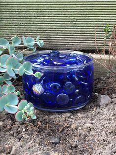 Vidste du godt at bier ikke kan svømme? Det vidste jeg heller ikke, men jeg har læst at der faktisk er mange bier som drukner i løbet af sommeren når de bliver tørstede og bevæger sig ud på for dybt vand.  Drikkestedet her er lavet af et lille glas fyldt med blå pyntesten (mest for det dekorative element) og selvfølgelig vand. Så kan bierne drikke masser af vand, men uden at lide druknedøden.