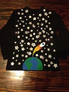 """100 days of school!!!   The assignment: put 100 items on a t-shirt and wear it to school for 100 points...be creative! I hand made the earth and spaceship to give the shirt a little more """"umph."""" I also added battery operated lights...so the shirt flashes. I think we nailed it:)"""