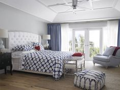 A contemporary coastal-style bedroom in shades of bright blue and pristine white. This master includes a set of glass-faced French doors that lead out onto the balcony in the midst of  the palms.