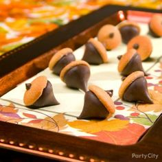 "chocolate-cookie acorns on a leafy platter Put together chocolate kisses & mini wafer cookies to make ""acorns"" Use corn syrup or vanilla extract to attach the cookie to the chocolate kiss, then create the acorn ""stem"" by adding a chocolate chip. For display, choose a napkin with fall foliage on it and layer it on a richly hued serving tray.Thanksgiving Appetizer and Dessert Ideas - Party City"