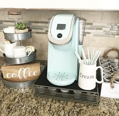 This coffee bar idea for the kitchen counter makes use of a small space with the mini Keurig coffee maker and serving tray. The homeowner has placed their coffee pods in a K-cup coffee pod holder tray that sits under the coffee maker to save space. Coffee Counter, Coffee Bars In Kitchen, Coffee Bar Home, Home Coffee Stations, Kitchen Small, Coffee Theme Kitchen, Cafe Themed Kitchen, Bar Kitchen, Kitchen Stove