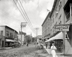 """New York circa 1909. """"Broadway -- Saranac Lake, Adirondack Mountains."""" Revisiting the scene glimpsed earlier here, with the addition of a shy pedestrian. Note the sly signage of """"Ernest Crice, hustling newsboy,"""" who cheekily gives his address as """"Flatiron Building."""" 8x10 glass negative."""